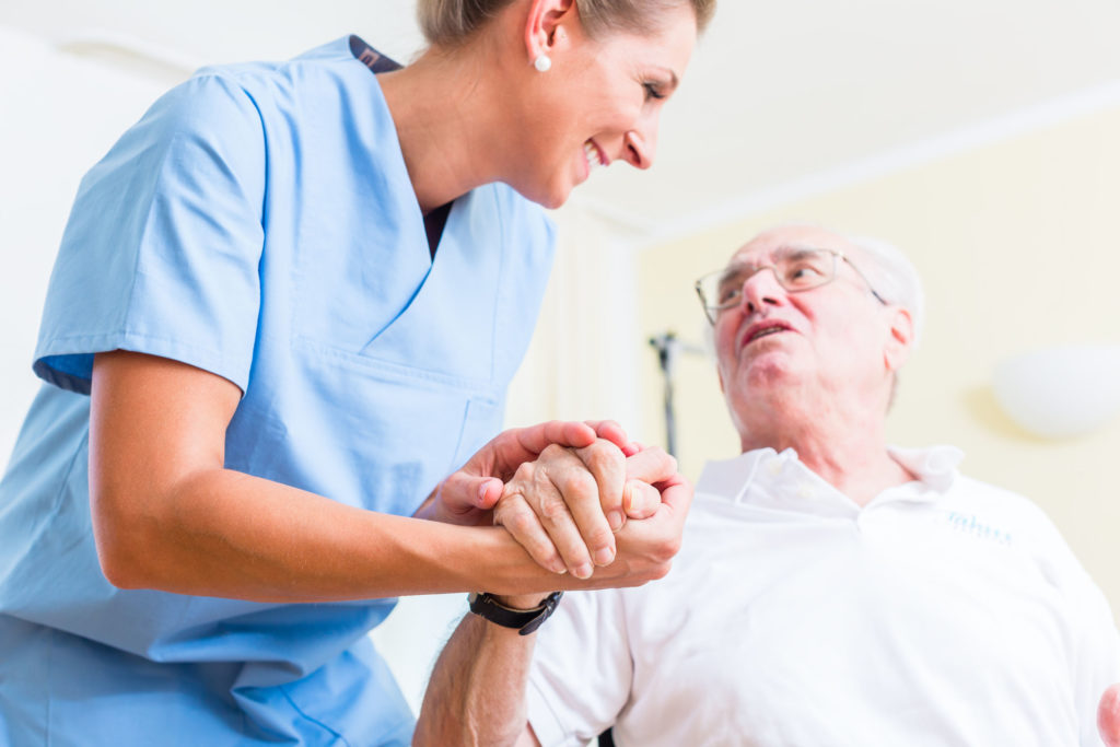 47846451 - nurse holding hand of senior man in rest home