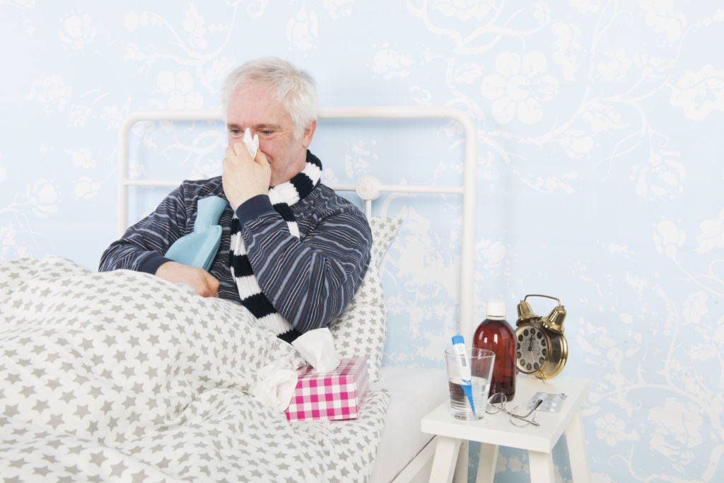 53874685 - senior man sick in bed with hot water bottle and thermometer